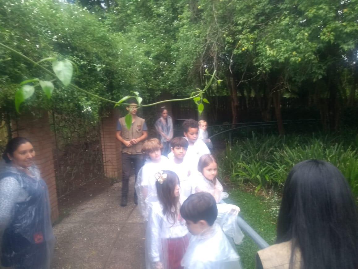 Foto: Divulgação. Crianças com capa de chuva observam explicação da orientadora em atividade no Jardim das Sensações. Professora acompanha a turma.